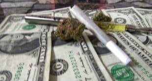 Marijuana joint and vape on top of cash