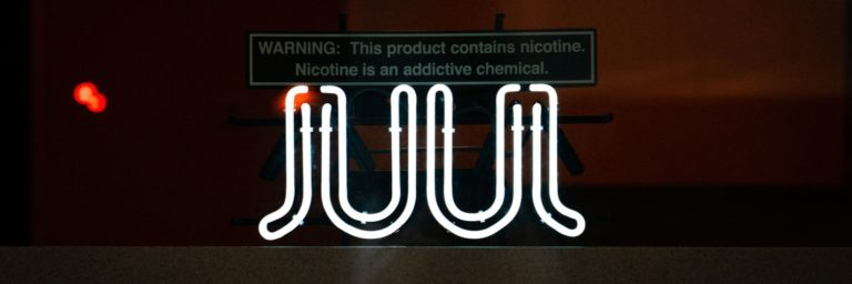 Neon JUUL sign lit against a dark background warns of nicotine content