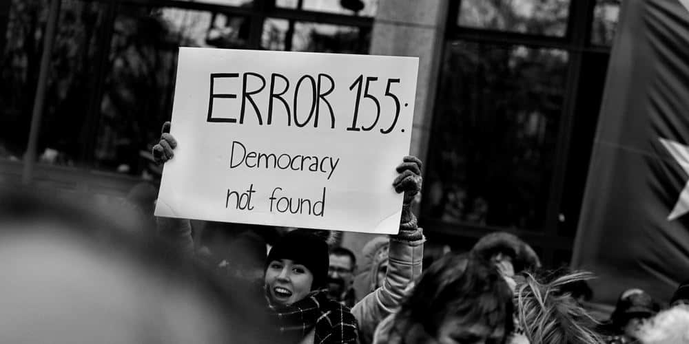 "a woman holds a sign that says, ""ERROR 155: Democracy not found"""