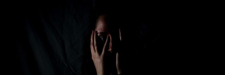 a woman looks afraid, holding her face, maybe as she experiences temporary psychiatric symptoms like paranoia