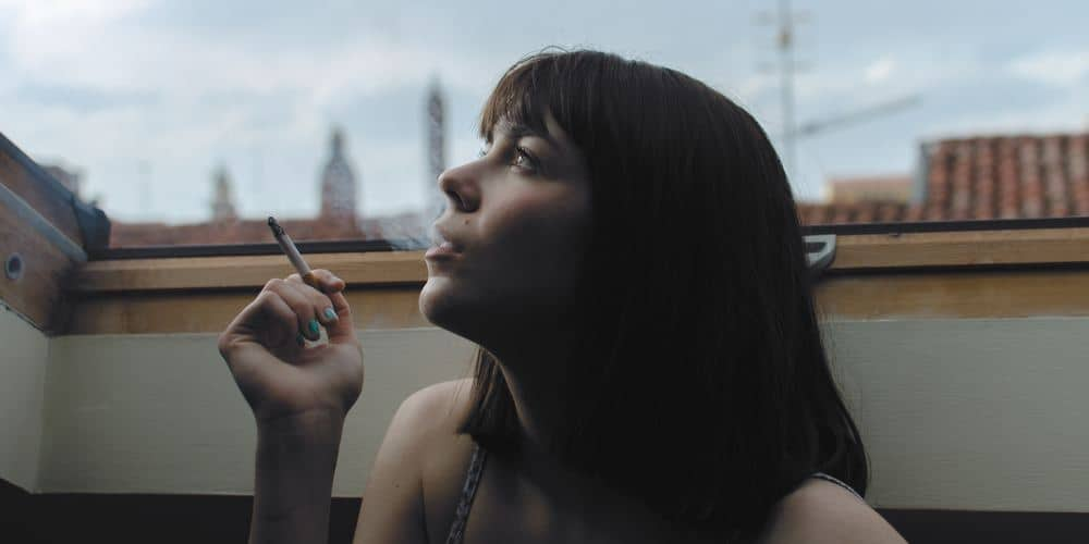 a woman exhales smoke which increases harmful lung bacteria