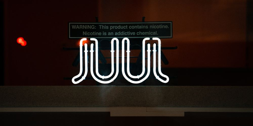 Neon JUUL sign at night against dark background
