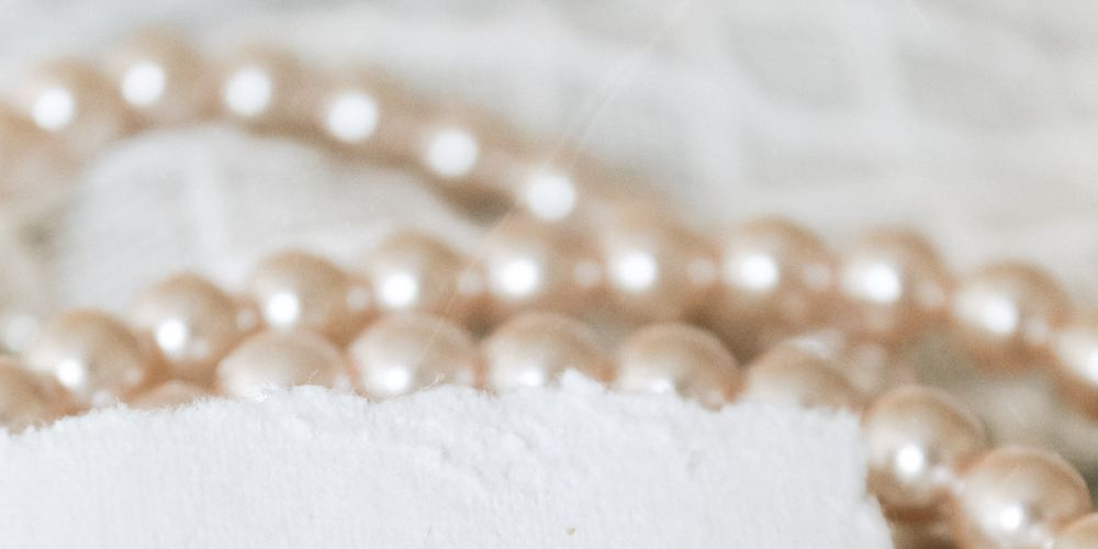 close up view of pearls on white fabric