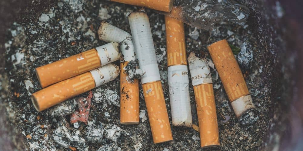 a dirty ashtray full of cigarette butts