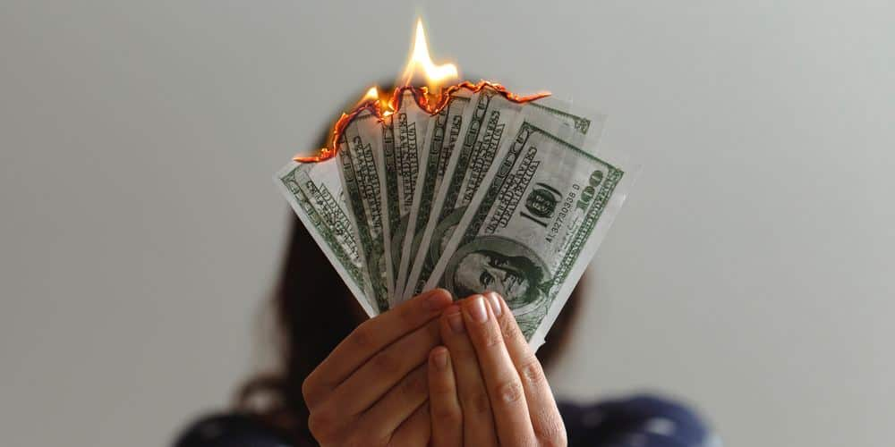 A person holds a handful of $100 bills, on fire