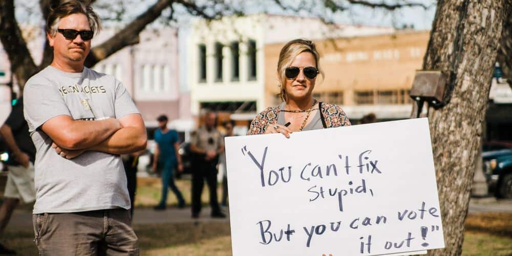 """man, woman standing holding a sign that says, """"You can't fix stupid, but you can vote it out!"""""""