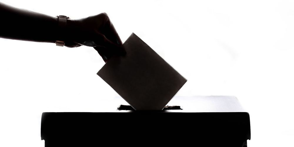 A hand in shadow drops a ballot into a voting box